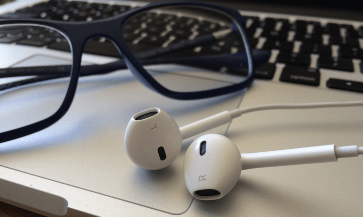 ecommerce podcasts: glasses and earphones on a laptop